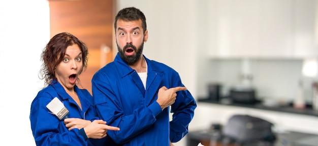 Pintores, apontando o dedo para o lado com um rosto surpreso em casa