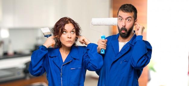 Pintores, cobrindo os ouvidos com as mãos em casa