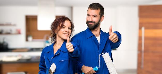 Pintores dando um polegar para cima gesto e sorrindo em casa