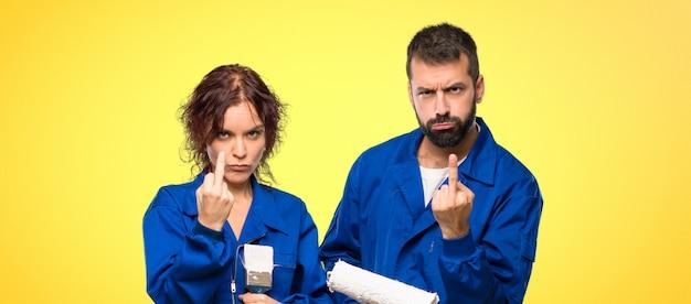 Pintores fazendo gesto de chifre. expressão negativa em fundo colorido