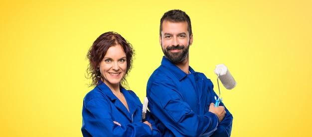 Pintores, mantendo os braços cruzados em posição lateral, enquanto sorrindo sobre fundo colorido