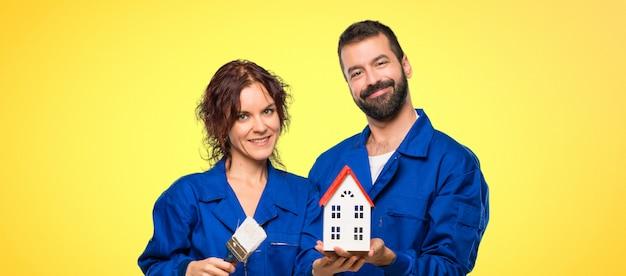 Pintores segurando uma casinha em fundo colorido