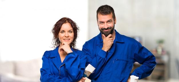 Pintores sorrindo e olhando para a frente com cara confiante em casa