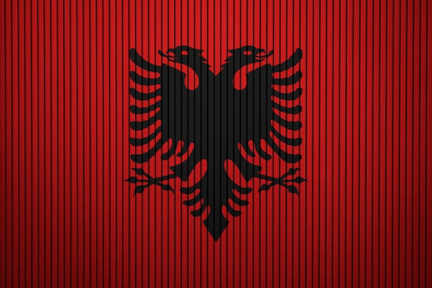 Pintou a bandeira nacional da albânia em uma parede de concreto