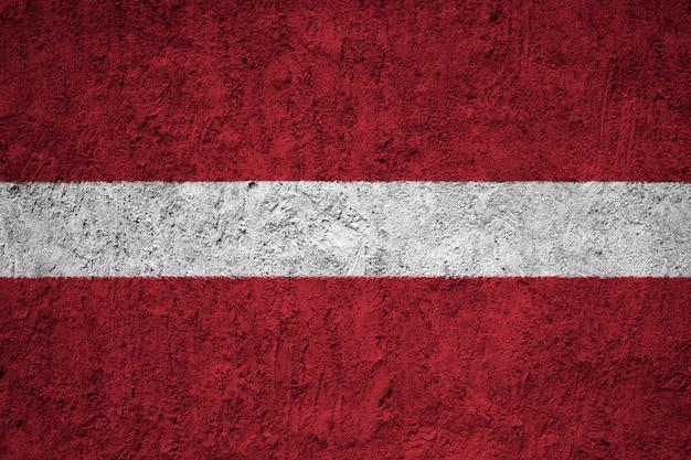 Pintou a bandeira nacional da letónia em uma parede de concreto