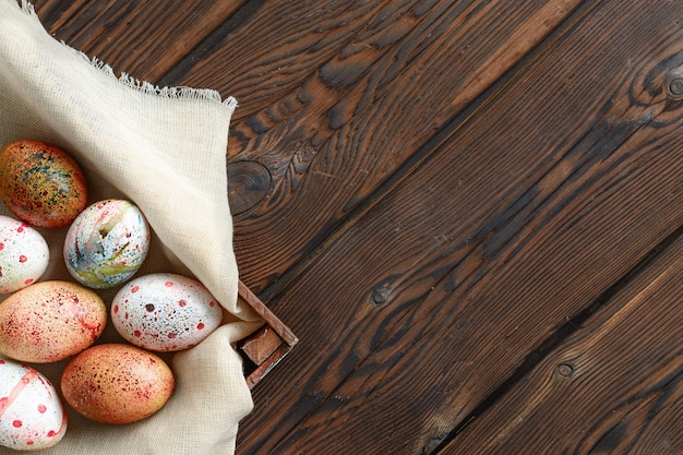 Pintou ovos de páscoa coloridos na lona na caixa de madeira escura no fundo de madeira