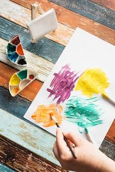 Pintura a mão da pessoa em papel branco sobre textura de madeira