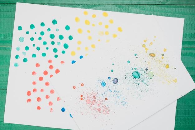 Pintura abstrata manchada multicolorida em papel branco sobre a mesa verde