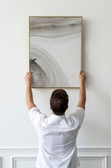 Pintura abstrata sendo pendurada por um jovem em uma parede branca mínima