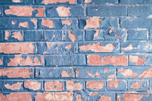 Pintura azul descascada em parede de tijolo vermelho