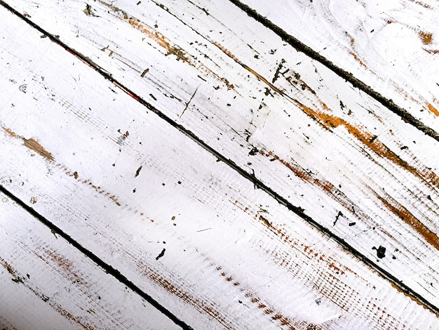 Pintura branca raspada em tábuas de madeira alinhadas diagonalmente