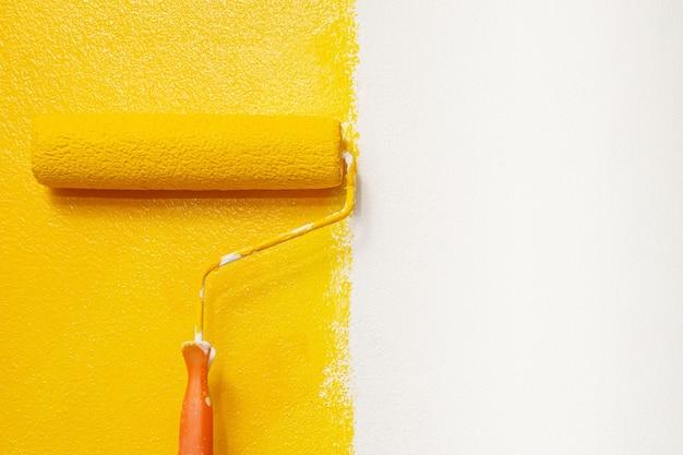 Pintura com escova de rolo, pintura do trabalhador na superfície pintura do apartamento, reformando com tinta amarela.
