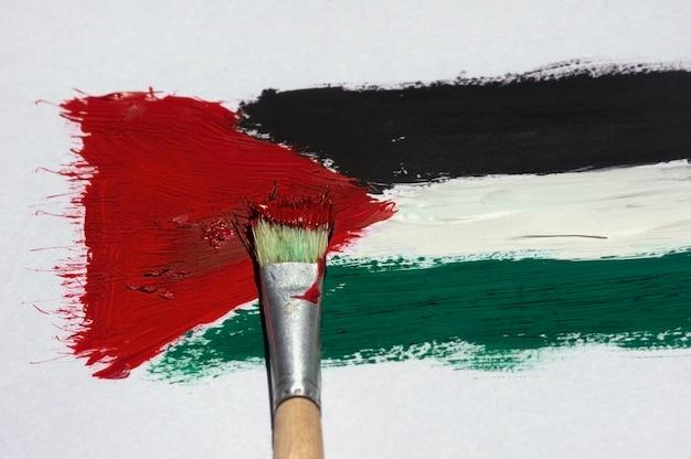 Pintura com pincel da bandeira da palestina em um papel para plano de fundo e papel de parede, foco selecionado.