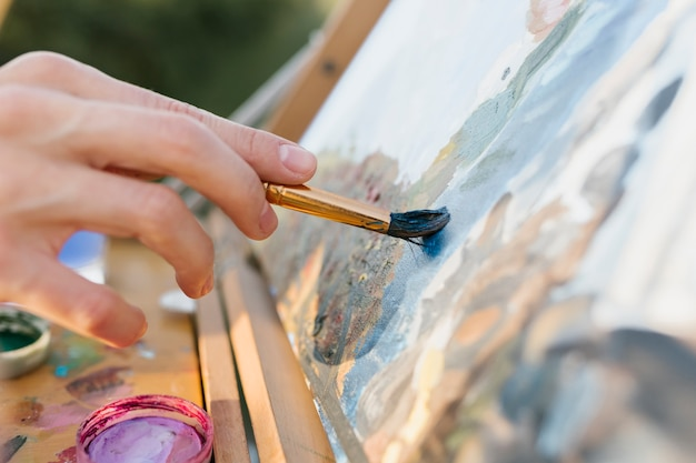 Pintura criativa da mão do close-up da mulher