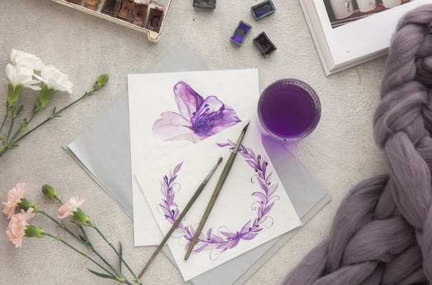 Pintura criativa de tintas aquarela brilhantes, lápis de cor, pincéis para desenhar flores. vista do topo