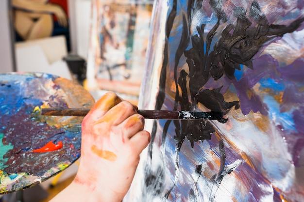 Pintura da mão do artista com pincelada preta na lona