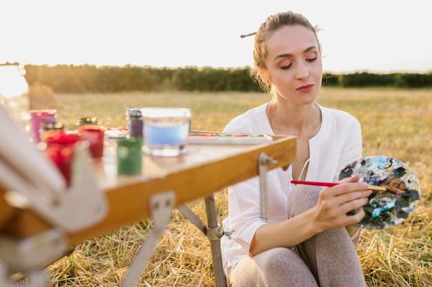 Pintura de mão jovem artista na natureza