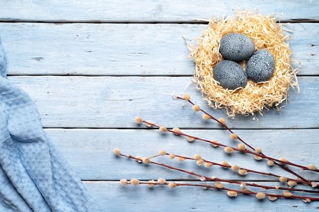 Pintura de ovos de páscoa com tinturas naturais de plantas, flores de hibisco do chá em um fundo azul de madeira