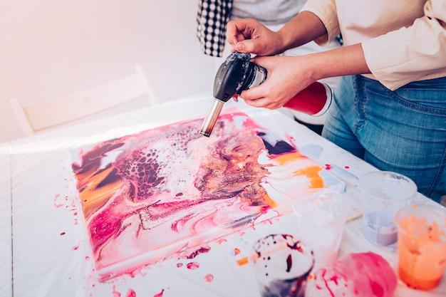 Pintura de secagem. close de uma artista profissional e talentosa secando sua pintura em mármore