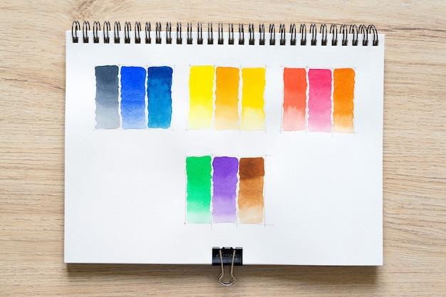 Pintura em aquarela sobre papel de caderno branco com fundo de madeira. coleção de tonalidades coloridas em papel branco. conjunto de pincel aquarela multicolorido. fechar-se.