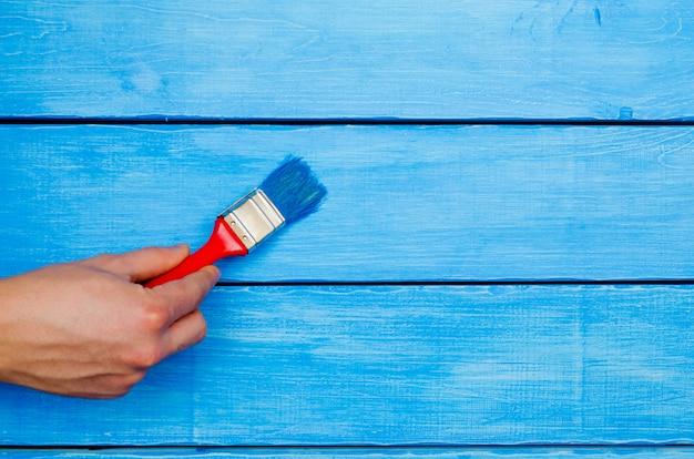Pintura em madeira, mão com um pincel, madeira azul