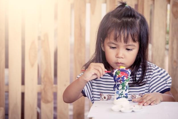 Pintura infantil, menina linda que se diverte para pintar em boneca de estuque juntos