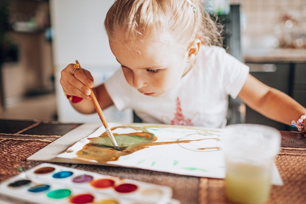 Pintura loura bonita da menina com cores do pincel e de água na cozinha.