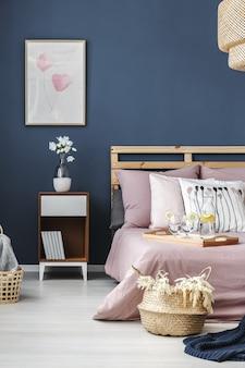 Pintura simples na parede azul acima da mesinha de cabeceira de madeira com flores brancas em um vaso branco