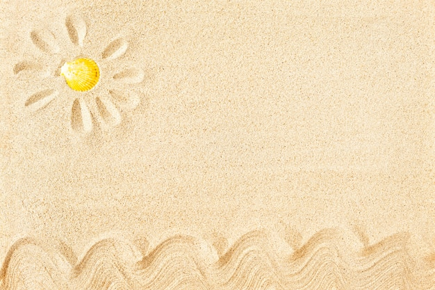 Pintura solar na areia com concha amarela, vista superior Foto Premium