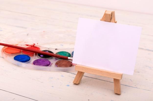 Pinturas coloridas da aguarela em uma caixa com pincel.