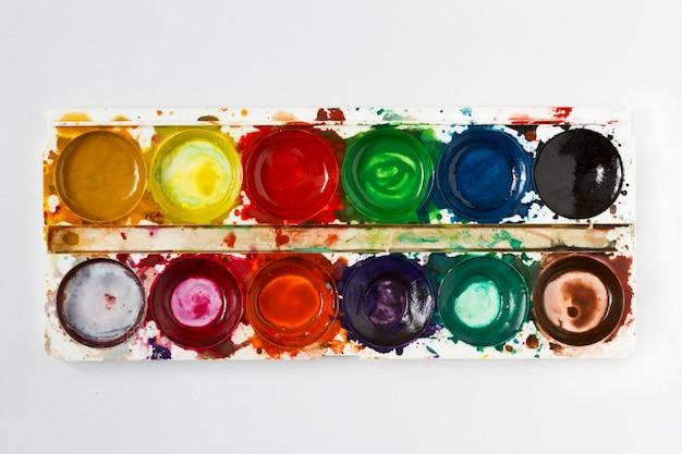 Pinturas da aguarela das crianças usadas no fundo claro.