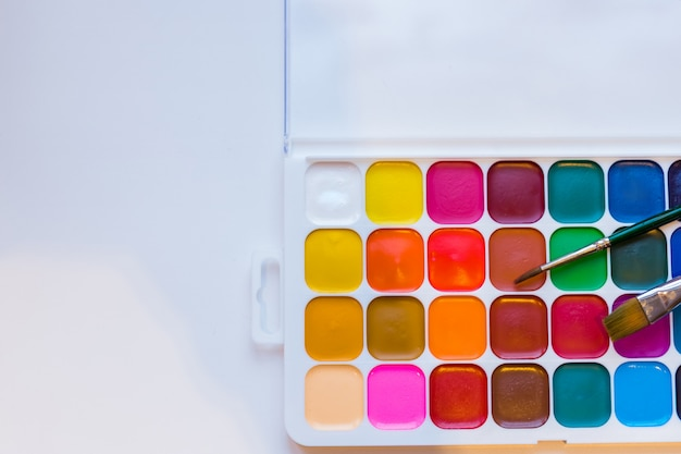 Pinturas e escovas da cor de água em um fundo branco. aulas de pintura. espaço da cópia