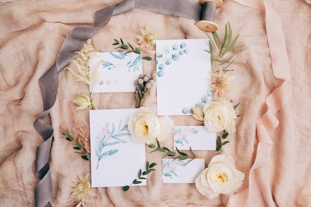 Pinturas em aquarela, fitas, rosas, galhos verdes e flores silvestres estendem-se sobre uma tela lindamente espalhada
