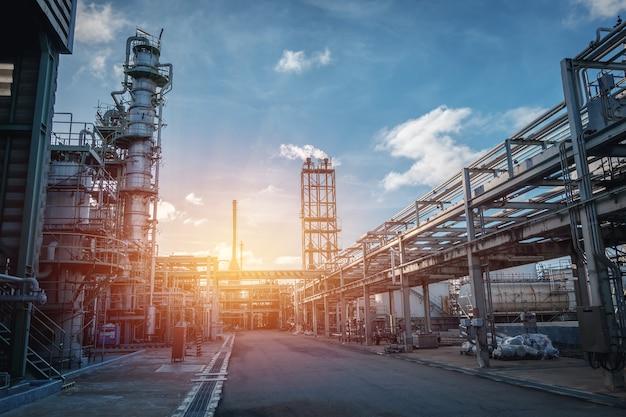 Pipeline e suporte de tubos da planta industrial de petróleo com céu pôr do sol