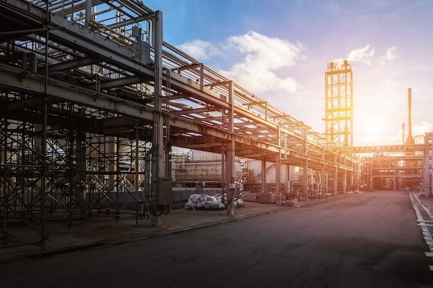 Pipeline e suporte de tubos da planta industrial de petróleo com fundo do céu por do sol