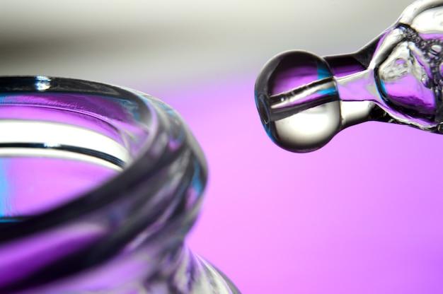 Pipeta cosmética com gotas de um líquido transparente e um frasco, close-up sobre um fundo colorido.