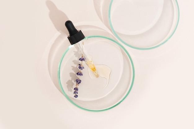 Pipeta de soro cosmético em uma placa de petri de cor lavanda clara sobre um fundo bege. cosmetologia, produtos farmacêuticos. peeling de ácido, óleo facial, colágeno.