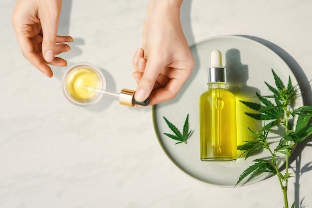 Pipete com óleo cosmético cbd em mãos femininas sobre uma mesa com uma garrafa de óleo de cannabis e folhas de cânhamo, maconha