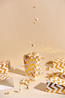Pipoca caseira crocante fresca salgada em copo de papel dourado na superfície bege da moda