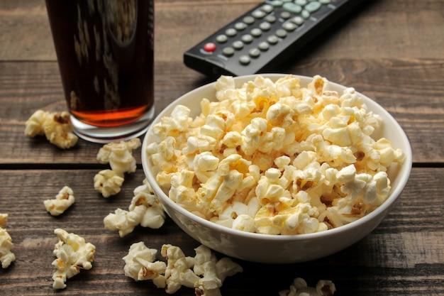 Pipoca, coca-cola e controle remoto de tv em uma mesa de madeira marrom, o conceito de assistir filmes em casa.