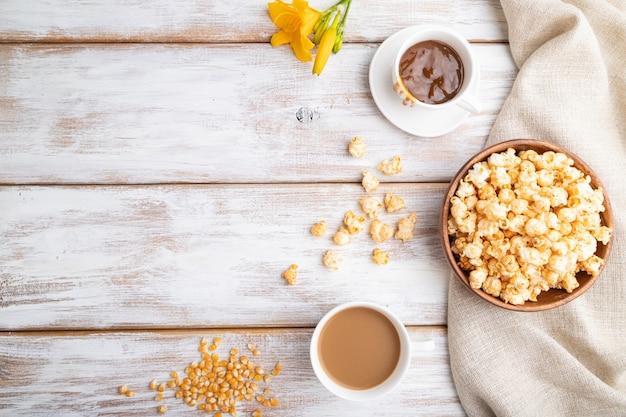 Pipoca com caramelo em tigela de madeira e uma xícara de café