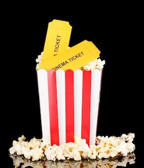 Pipoca com ingressos de cinema isoladas em preto