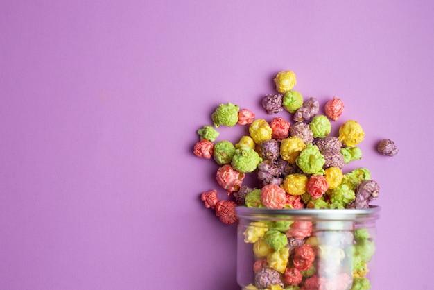 Pipoca com sabor de frutas multicoloridas em copos de vidro rosa