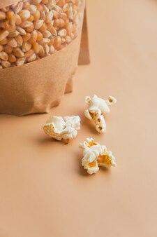 Pipoca cozida em uma tigela de vidro e grãos de milho em uma caixa de papel sobre uma superfície bege