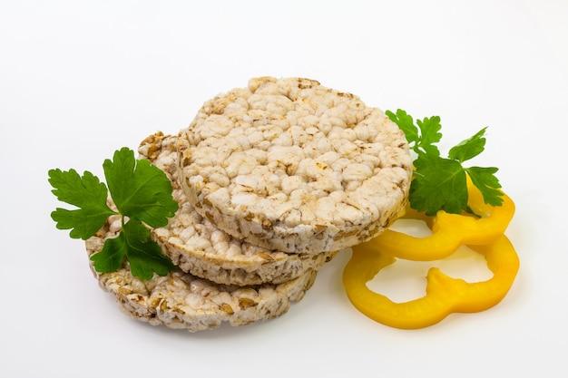 Pipoca crocante redonda e pão de arroz com anéis de pimentão amarelo e ervas picantes. isolado em um fundo branco.