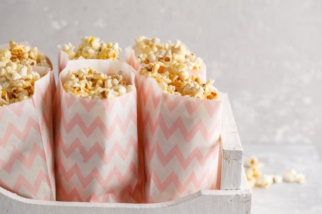 Pipoca de caramelo dourada em sacos de papel rosa em uma caixa de madeira branca, copie o espaço