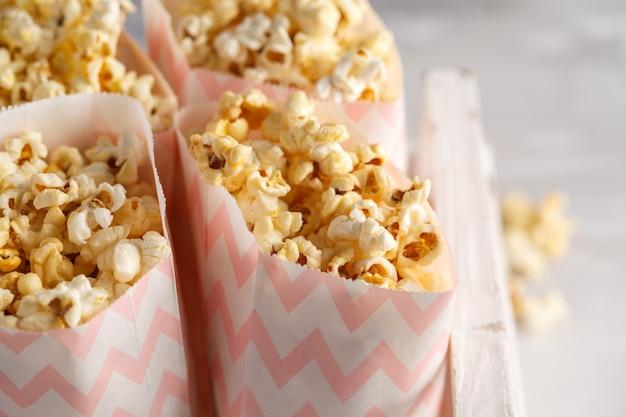 Pipoca de caramelo dourado em sacos de papel rosa em uma caixa de madeira branca.