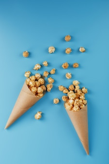 Pipoca de caramelo em um envelope de papel sobre um fundo azul. elogios deliciosos por assistir filmes, seriados, desenhos animados espaço livre, close-up. conceito minimalista.