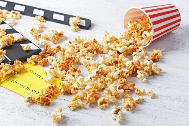 Pipoca de caramelo, ingressos e badalo de cinema na mesa de madeira