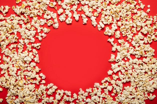 Pipoca deliciosa sobre um fundo vermelho. vista de cima